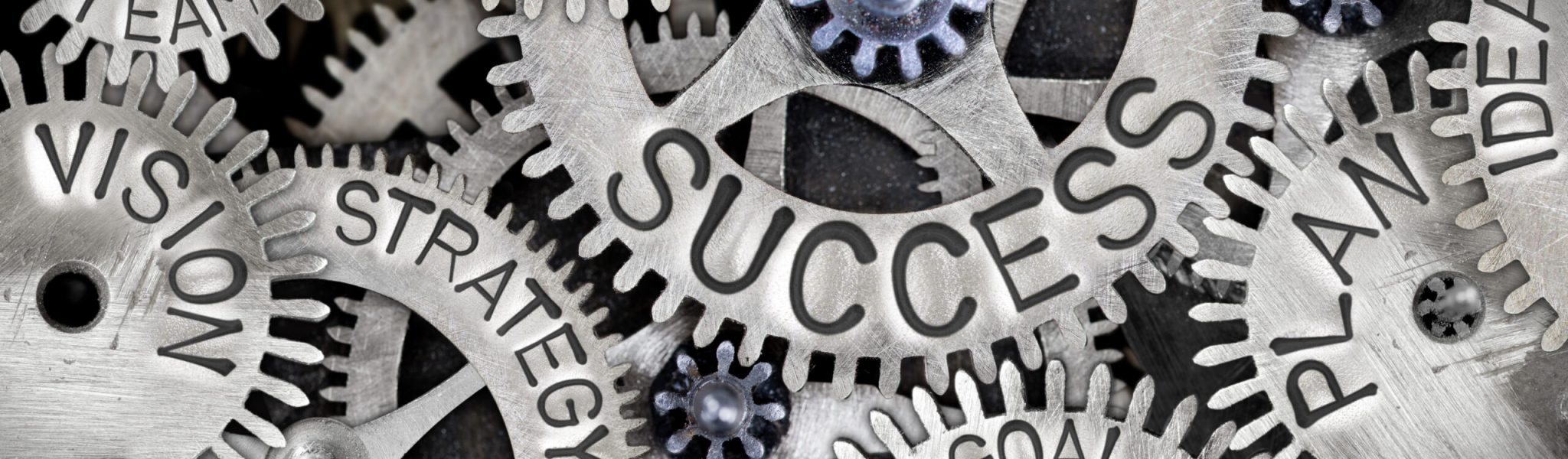 Macro photo of tooth wheel mechanism with SUCCESS concept letters